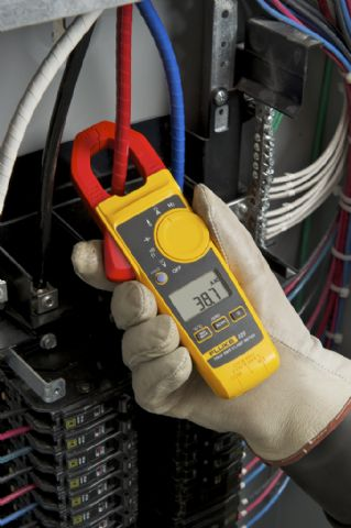 hand holding Fluke 325 400a ac/dc true rms clampmeter with temp