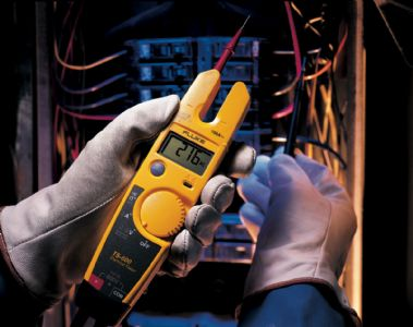 Hands using Fluke T5-600 electrical tester