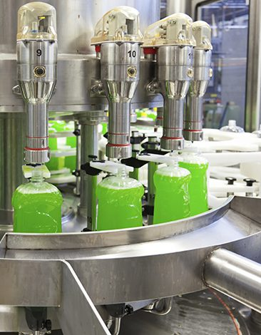 Bottles in a production line being filled with liquid